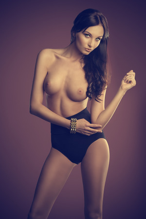 naked brunette girl posing in topless with black paints and golden bracelet.