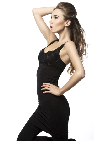 flowing hair: charming woman with perfect silhouette in fashion pose with stylish make-up, elegant black dress and flowing wavy hair