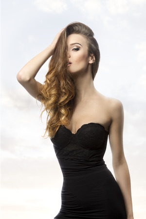 sexy black dress: sexy woman with long wavy flowing hair on the face, sexy black dress and cute make-up, in sensual pose in fashion shoot