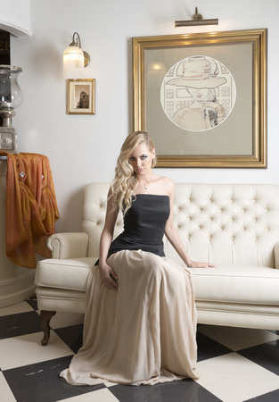 pretty young blond woman , setting on white sofa in very elegant ambient , wearing black top with hair style photo