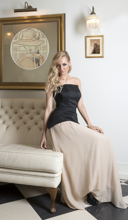 nice blonfd woman, sitting on white sofa in very elegant ambient , wearing black top with hair style photo