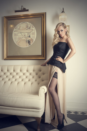blond elegant woman with hair style and curly hair , posing near a white sofa showing leg with stocking