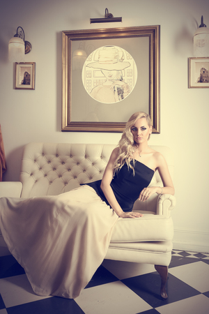blond woman with hair style , in elegant interior , laying on white sofa and looking in camera photo