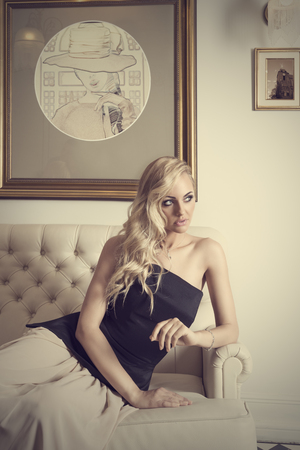 elegant girl with curly hair , sitting on white sofa , in luxury interior , she is looking on one side  photo