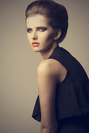 vogue sexy woman with elegant hair-style, stylish make-up and trendy black dress Stock Photo - 30528266