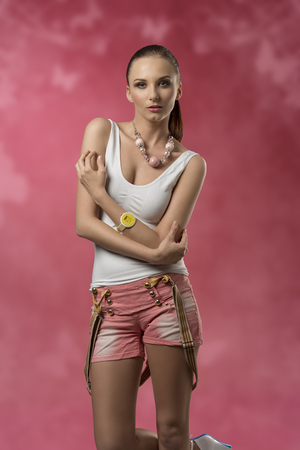 brunette woman in sensual pose with casual modern style wearing sexy shorts, wrist watch and suspenders Stock Photo