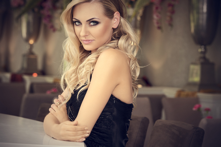 night club interior: romantic portrait of cute beautiful blond with curly hair in luxury bar . loooking in camera smiling Stock Photo