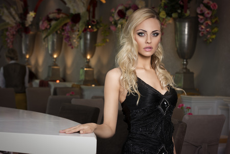 hair do: beautiful blond girl in black dress near a luxory bar , posing and looking in camera . she has hair do Stock Photo