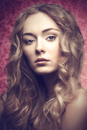 Short portrait of blonde beautiful young girl with long curly hair on pink backgroung is looking in camera photo