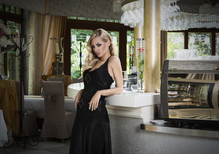 sexy blond , in elegant black dress waiting for people near a cafe in a elegant and luxury restaurant  Standard-Bild