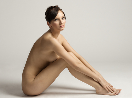 desnudo artistico: impresionante cuerpo desnudo de una mujer muy sensual y hermosa belleza en pose, mirando en la cámara suavemente, la piel natural Foto de archivo