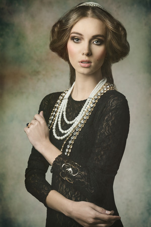 cute brunette girl posing in fantasy portrait wearing like a antique aristocratic lady with precious brilliant crown, vintage hair-style and brilliant jewellery