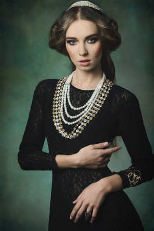 hairstyle woman: antique aristocratic lady with elegant dress, precious jewellery, brilliant crown and medieval hair-style. Fantasy fashion shoot