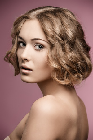 silky hair: beauty shoot of pretty girl with short curly blonde hair-cut and natural make-up.