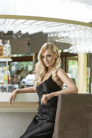night club interior: romantic portrait of elegand blond woman , sitting and waiting for someone in a luxury bar