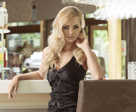 romantic vintage portrait of elegand blond woman , sitting and waiting for someone in a luxury bar