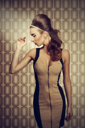 dignified: Young, beautiful woman in fitted cream and black dress is standing sideways. She has got big blue eyes, brown big hairstyle and she is wearing hairband and pearls on her ears. She has got red lips and highlighted eyes. Stock Photo