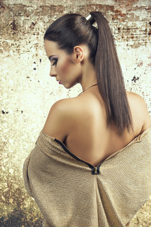 Beautiful woman shows her backs. She wears sparkling, smart, gold dress and beautifu.She has brown, long, straight hair clipped together. She is wearing purple make up. photo