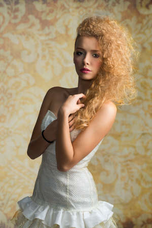 Young, blonde, pretty girl with curly hairstyle and romantic look. She is wearing white, gorgeous dress with a loop and colorful makeup. photo