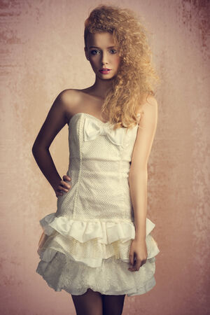 Young, blonde, pretty girl with curly hairstyle and romantic look. She is wearing white, gorgeous dress with a loop and colorful makeup. She is looking at camera. photo