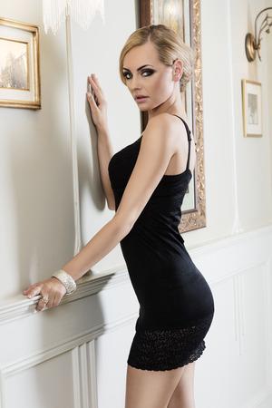 vrouw blond: prachtige blonde vrouw in korte sexy zwarte jurk in de buurt van een muur in een zeer luxe overdekt, is ze op zoek in de camera