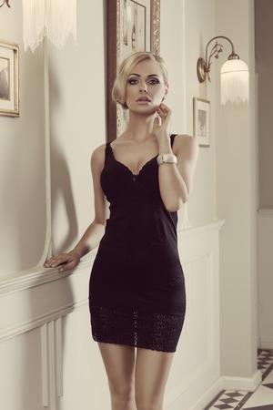 stunning blond sensual woman , wearing black short dress, in a very elegant ambient , she is looking in camera Standard-Bild