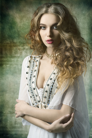 victorian lady: lovely dame with antique style and golden jewellery posing with curly long hair and looking in camera