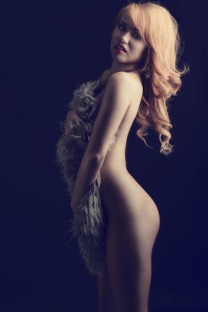 nude woman: Sexy mujer, desnudo con el pelo jengibre cubre su cuerpo con piel mullida. Ella tiene maquillaje agradable y hermosas joyas.