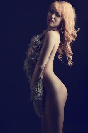 artistic nude: Sexy, nude woman with ginger hair cover her body with fluffy fur. She has got nice makeup and beautiful jewellery.