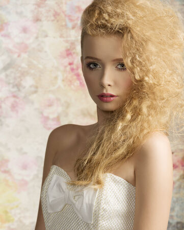 fashion shoot: close-up fashion shoot of cute blonde woman with stylish hair-style, natural make-up and elegant white dress looking in camera