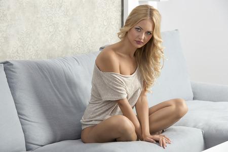 modelos posando: Hermosa mujer joven está sentado en el sofá. Ella lleva un beige, puente cómodo y tiene un buen corte de pelo.