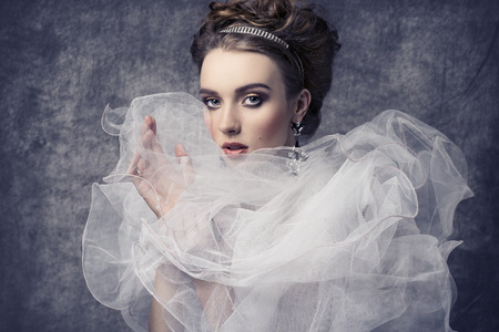 fashion shoot of pretty woman with romantic retro dame style. Wearing baroque dress with frill veil collar, precious earrings and tiara in the hair-style, elegant make-up Foto de archivo