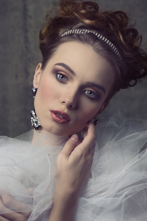 a frill: close-up portrait of sensual woman with romantic retro style posing with shiny tiara in the elegant hair-style, precious  earrings, vintage romantic dress with frill veil collar. Aristocratic vintage dame