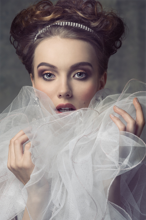 a frill: close-up shoot  of beauty adorned like aristocratic vintage dame with shiny tiara in the elegant hair-style, precious  earrings, vintage romantic dress with frill veil collar.