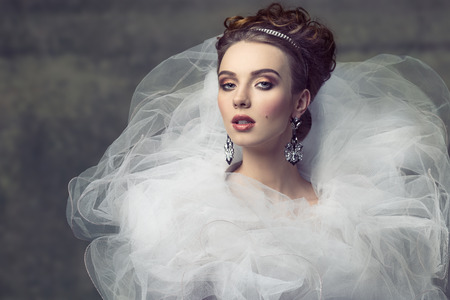 sexy bride: cute young girl wearing like sophisticated dame with creative romantic dress, elegant hair-style, shiny tiara, precious earrings and stylish make-up. Looking in camera with arrogant expression