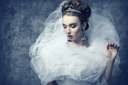 sexy bride: charming lady wearing like sophisticated dame with baroque romantic dress, elegant hair-style, shiny tiara, precious earrings and stylish make-up. Stock Photo