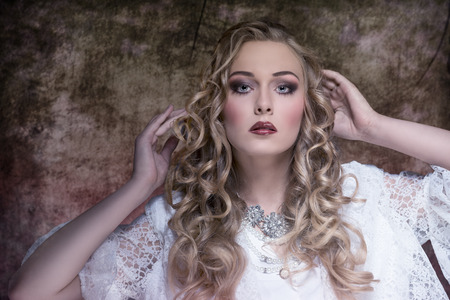 lovely blonde female with aristocratic style posing with long curly hair, stylish make-up, vintage elegant dress and precious necklace