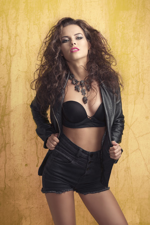fashion shoot: curly brunette female posing in fashion shoot with sexy rock style with bra, modern hair-style, stylish make-up, aggressive leather jacket, creative skull necklace