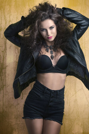 beautiful curly young lady posing with rock dark look in fashion portrait. Wearing sexy black bra under aggressive leather jacket, denim shorts and creative skull necklace