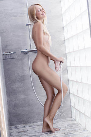 showering: Natural, blonde pretty woman in the bathroom. She is under the shower and she is splasching her body with water.