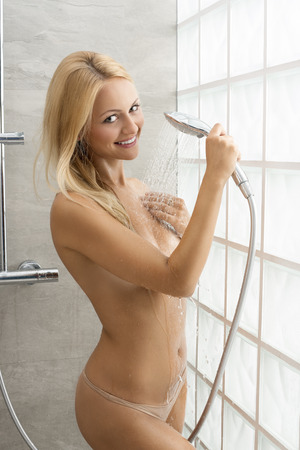 showering: Pretty, natural, fit blonde woman is taking a shower. She is happy and splashing water on her body. Stock Photo