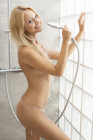 woman in shower: Happy, beautiful, natural, blonde woman under the shower. She has got blue eyes and perfect smile. Stock Photo