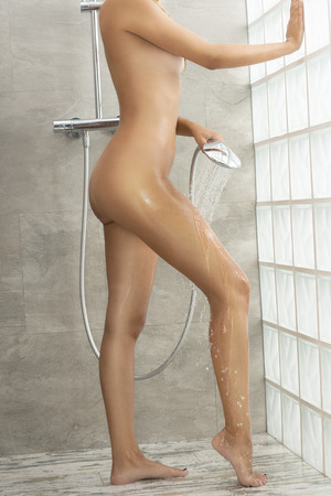 woman in shower: Natural, body, of woman under the shower. She is splashing water on her legs.