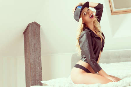 gril: Beautiful gril with long, blonde, curly hair is on the bed. She is wearing black underwear, leather jacket andd fullcap. She has got purple lips.