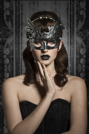 Mysterious, carnival, elegant, gorgeous female in silver mask with black lips and old fashioned hairstyle.