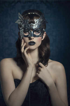 Beautiful, mysterious, sensual, woman with brown old fashion hairstyle, silver mask and dark makeup.
