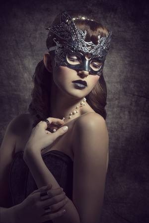 Gorgeous, mysterious female in carnival, silver mask, with brown long hair and dark make up wearing black dress.