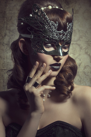 masquerade costumes: Beautiful, mysterious, magical woman in silver magical mask with black lips amd fantastic hairstyle.