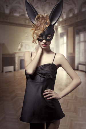 black satin: Charming, sexy Easter, black bunny in black,satin dress, red lips and wild, red hair.
