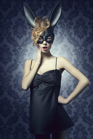Carnival, charming, funny sexy woman in black bunny costume, wild red hair, nice make up.